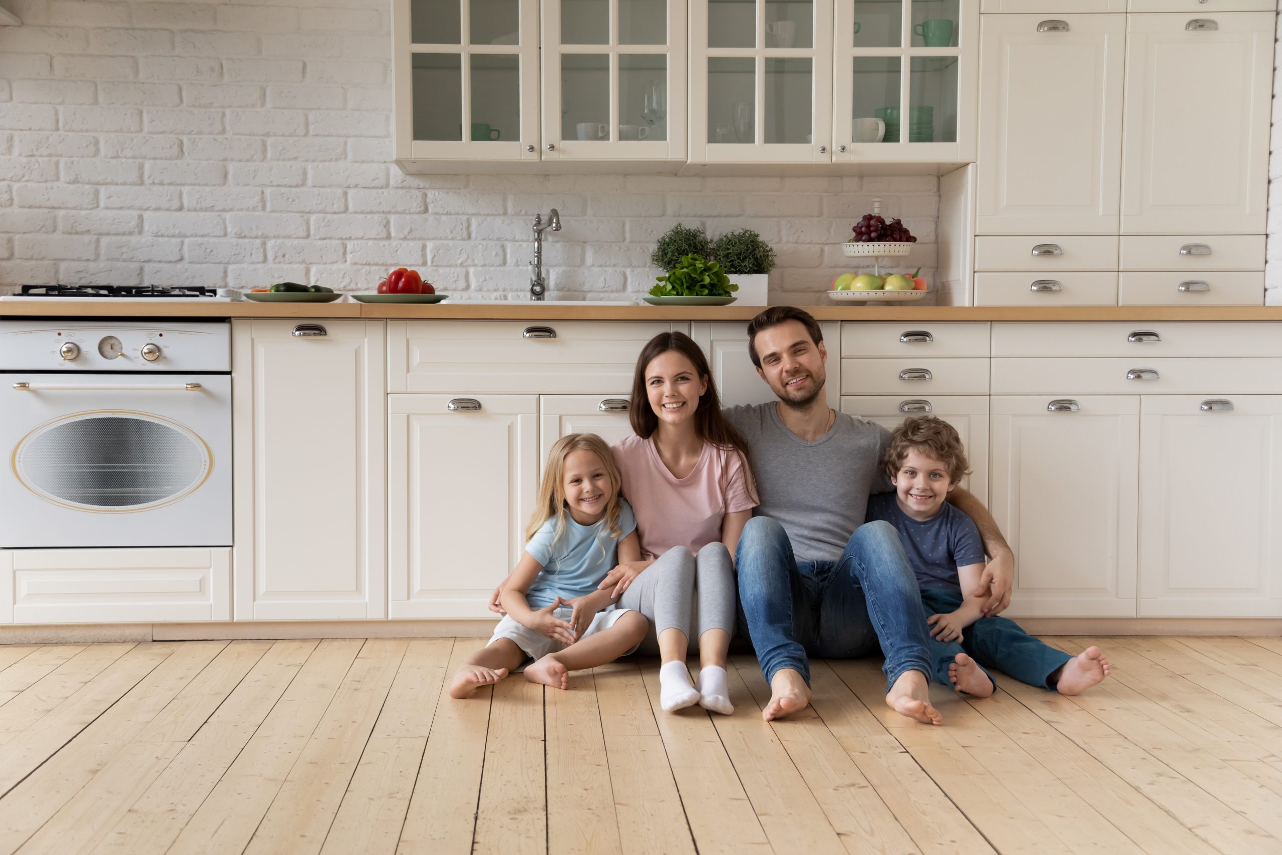 Young family of 4 sitting on the kitchen floor in their newly renovated modern white kitchen