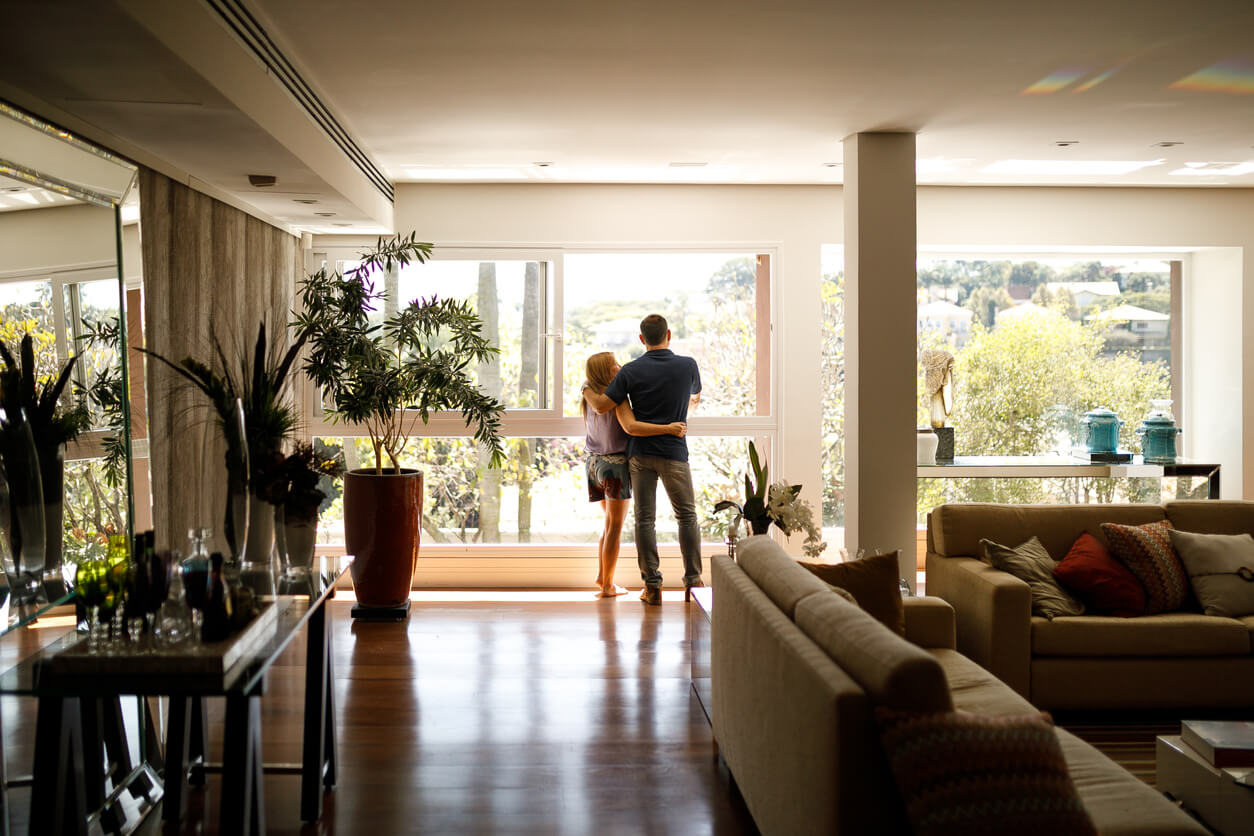Couple Looking Out Newly Installed Floor to Ceiling Windows